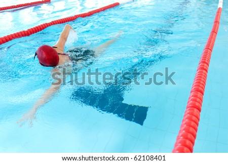 young woman swim on indoor pool. freestyle mode. - stock photo