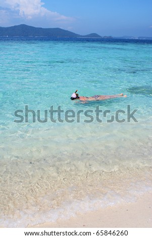 Young woman swimming and snorkeling in the clear water of Andaman Sea, Khai Nok Island, Thailand