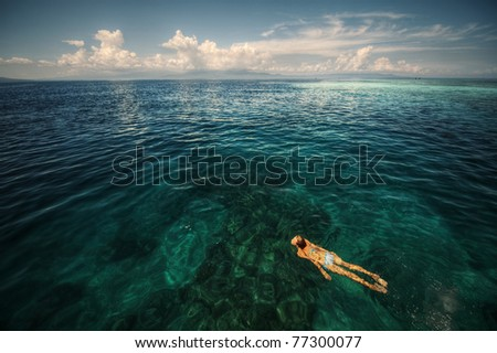 Young woman swimming over coral reef in transparent tropical sea. Bunaken island. Indonesia - stock photo