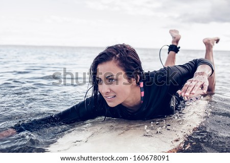 Young woman swimming over surfboard in the water at beach - stock photo