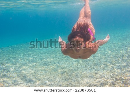 Young woman swimming undewater in the sea - stock photo