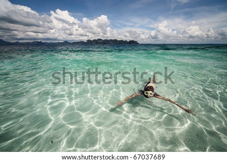 Young woman swimming with mask in clear sea - stock photo