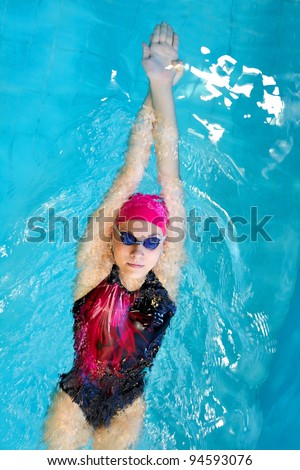 young woman swims on back in the pool