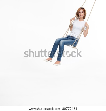 young woman swinging alone on a swing - stock photo