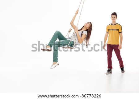 young woman swinging on a swing with handsome man looking - stock photo