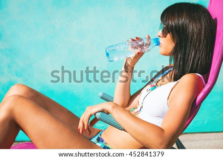 young woman take sunbath and drink water side view hot summer day