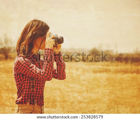 Young woman takes photographs with vintage photo camera in autumn outdoor. Vintage image - stock photo