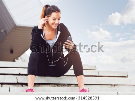 Young woman taking a break from exercising outside with cellphone - stock photo