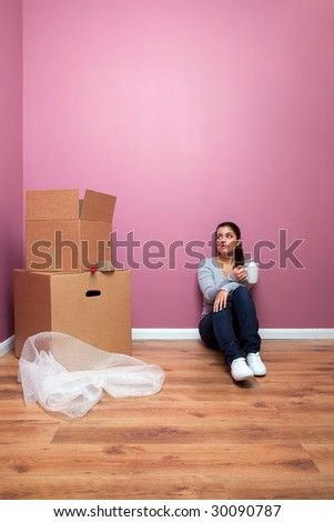 Young woman taking a break from packing during a home move. Plenty of copy space. - stock photo