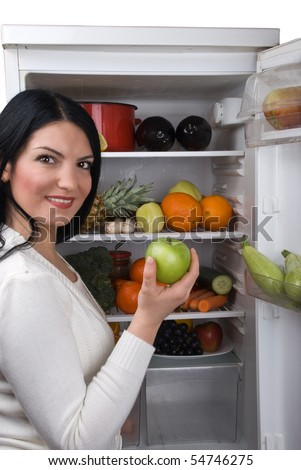 Young woman taking a green apple from her fridge full with fresh fruits and vegetables - stock photo