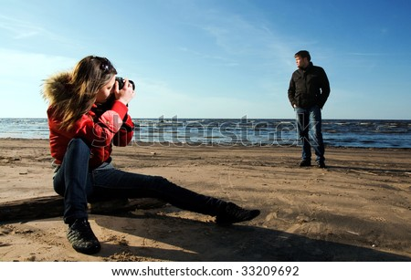 Young woman taking a photo of her boyfriend on the beach (Woman in focus) - stock photo