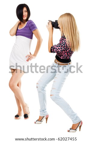Young woman taking a picture of pretty girl, white background - stock photo