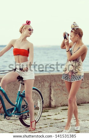 Young woman taking a picture with an old camera against a pier. Outdoor, lifestyle - stock photo
