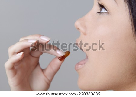 Young woman taking a pill - stock photo