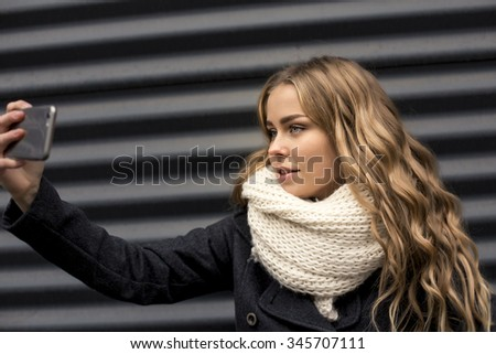 young woman taking a self portrait outdoors in winter - stock photo