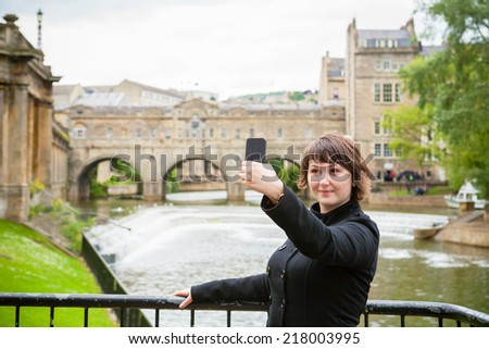 Young woman taking a selfie in front of Pulteney Bridge. Bath, Somerset, England, UK - stock photo