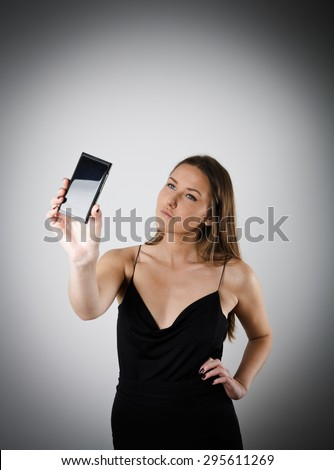 Young woman taking a selfie using her smartphone. Young woman is doing something. - stock photo