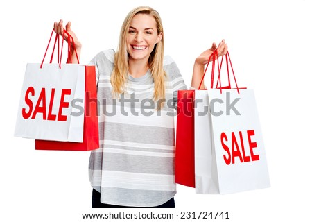 Young woman taking advantage of shopping sale with bags isolated on white - stock photo