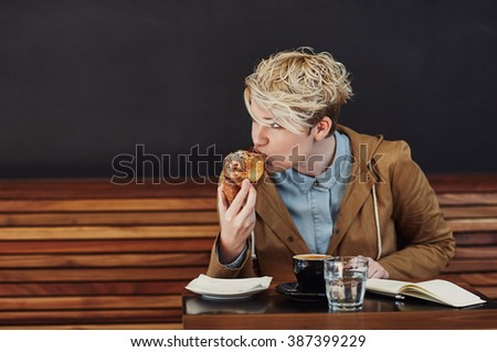 Young woman taking bite of croissant in a modern cafe - stock photo
