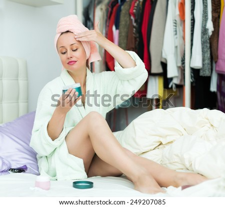 Young woman taking care of face skin with lotion