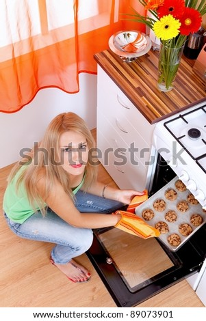 Young woman taking cookies out of oven - stock photo
