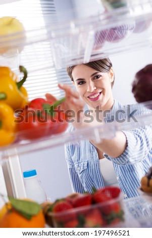 Young woman taking fresh healthy vegetables from refrigerator. - stock photo