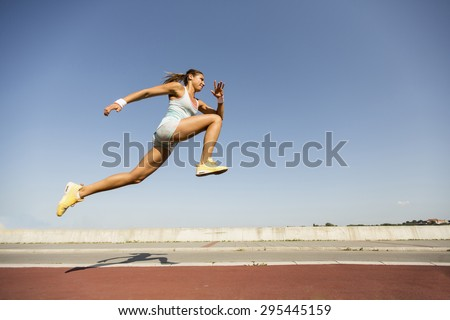 Young woman taking long jump - stock photo
