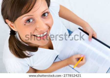 Young woman taking notes sitting on the bed isolated on white background