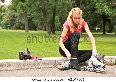 Young woman taking on roller skates - outdoors in park - stock photo