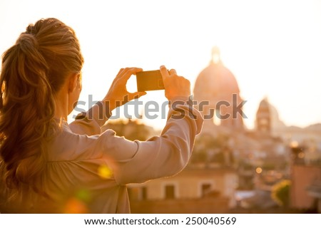 Young woman taking photo of rome panorama on sunset. rear view - stock photo