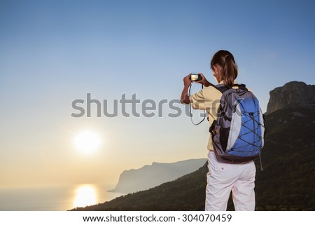 Young woman taking photo of sunrise in a mountain using compact camera