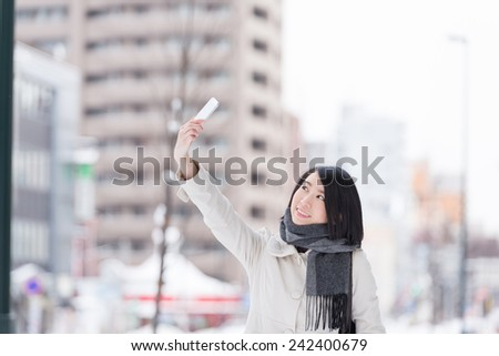 Young woman taking photo with smart phone. - stock photo
