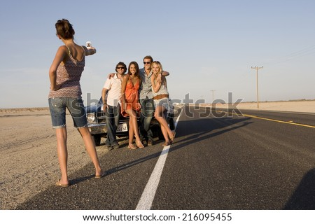 Young woman taking photograph of medium group of friends by car on open road, low angle view - stock photo