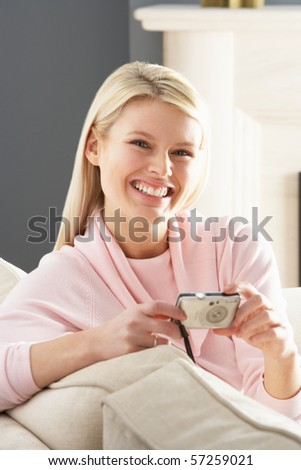 Young Woman Taking Photograph On Digital Camera At Home - stock photo