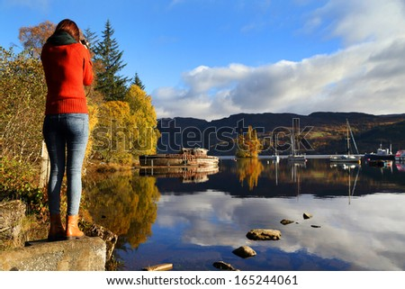 Young woman taking photos at Lochness, Scotland, Europe - stock photo