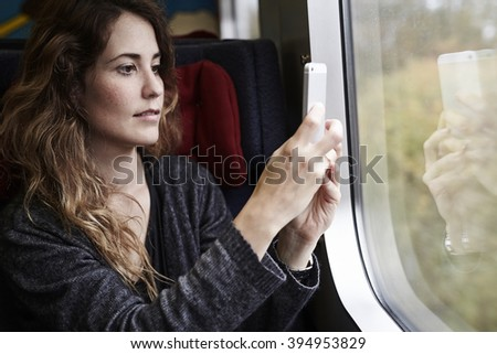 Young woman taking picture from train - stock photo