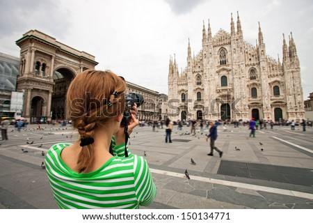 Young woman taking picture of Duomo di Milano (Milan Cathedral), Milan, Italy, motion blurred people on square