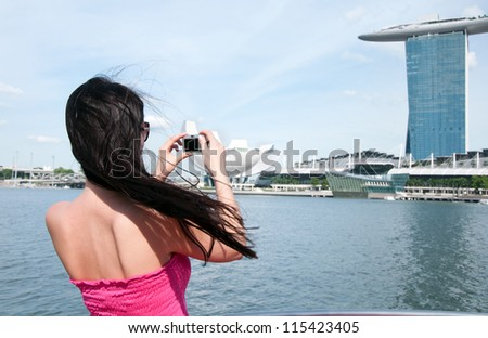 Young woman taking picture of Marina bay hotel in Singapore - stock photo