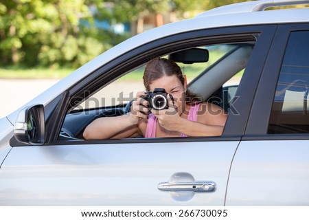 Young woman taking picture with camera through the car window - stock photo