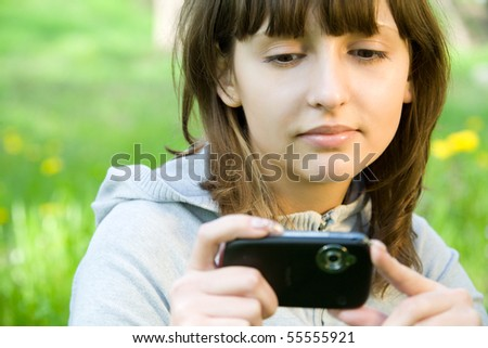 Young woman taking picture with digital camera over green grass - stock photo