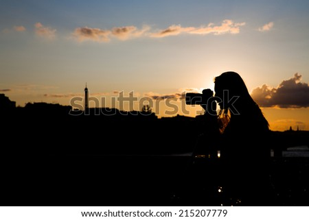 Young woman taking pictures at dusk on a bridge in Paris, capital of France, with the Eiffel Tower in the background and with colorful sky with clouds - stock photo