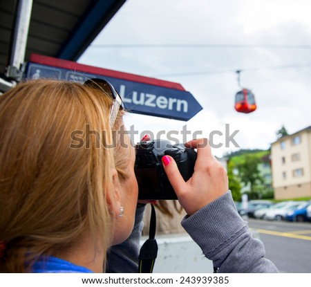 Young woman taking pictures in Kriens, Switzerland. European adventure, travel vacation, photography, outdoors and life style concept   - stock photo