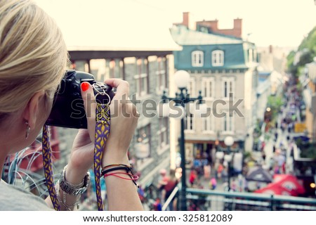 Young woman taking pictures on the busy rue  Petit Champlain in Quebec City, Canada. North American, adventure, travel vacation, photography, outdoors and life style concept - stock photo