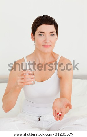 Young woman taking pills in her bedroom - stock photo