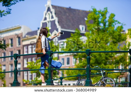 Young woman taking self portrait in european city outdoors. Young adult holding smartphone camera to take a picture of herself during her summer vacation in Amsterdam - stock photo