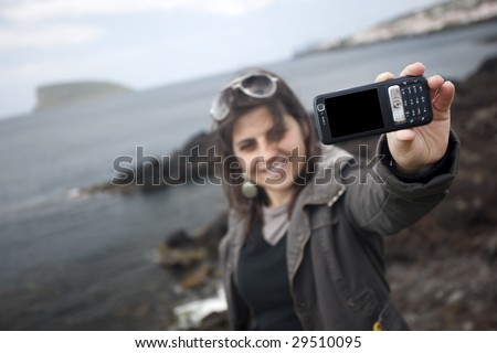 young woman taking self portrait with mobile phone camera - travel concept - stock photo