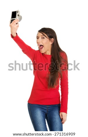 Young woman taking selfie with a camera. - stock photo