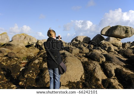 Young woman taking video shots of the granite rocks of the wild coast of Brittany, France - stock photo
