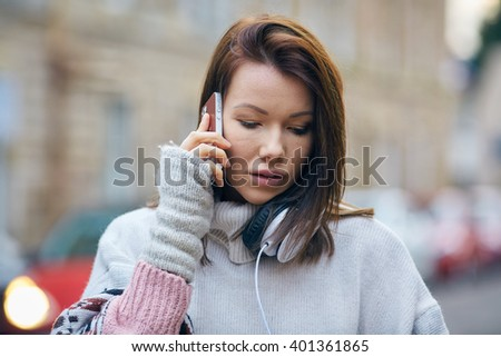 Young woman talk over her mobile, portrait taken on the street, urban background - stock photo