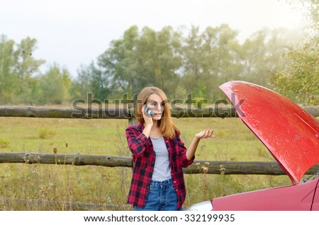 Young woman talking by phone near broken car with bonnet opened - stock photo
